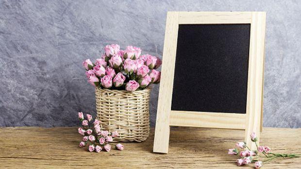 Tafel in Holzrahmen und Korb voller rosafarbener Rosen
