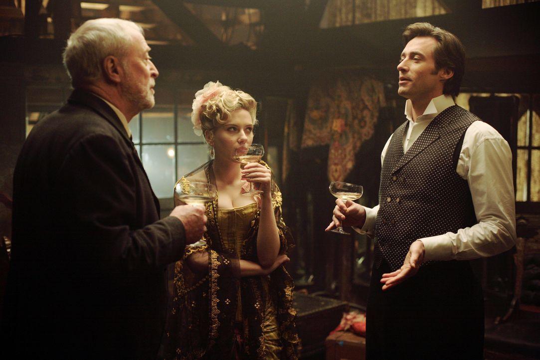 Stoßen auf eine gelungene Vorstellung an: Robert Angier (Hugh Jackman, r.), Cutter (Michael Caine, l.) und Olivia Wenscombe (Scarlett Johansson, M.)... - Bildquelle: Warner Television