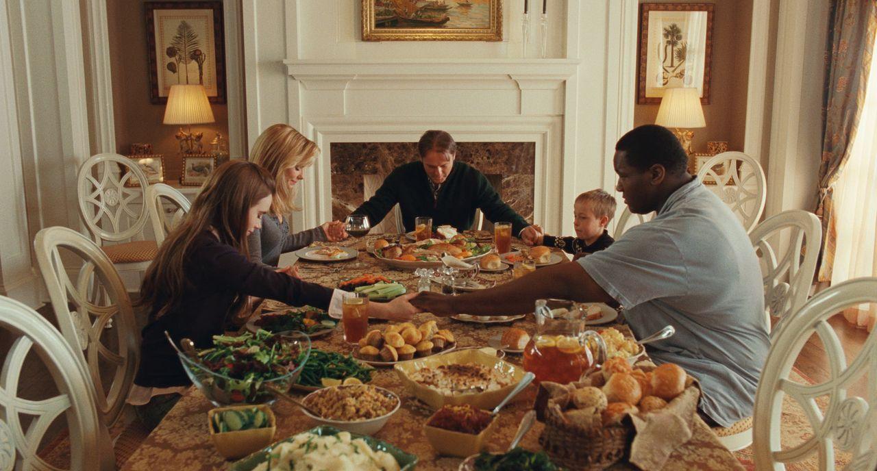 Der obdachlose afroamerikanische Jugendliche Michael Oher (Quinton Aaron, r.) wird von der Weißen Leigh Anne Tuohy (Sandra Bullock, 2.v.l.) und ihr... - Bildquelle: Warner Brothers