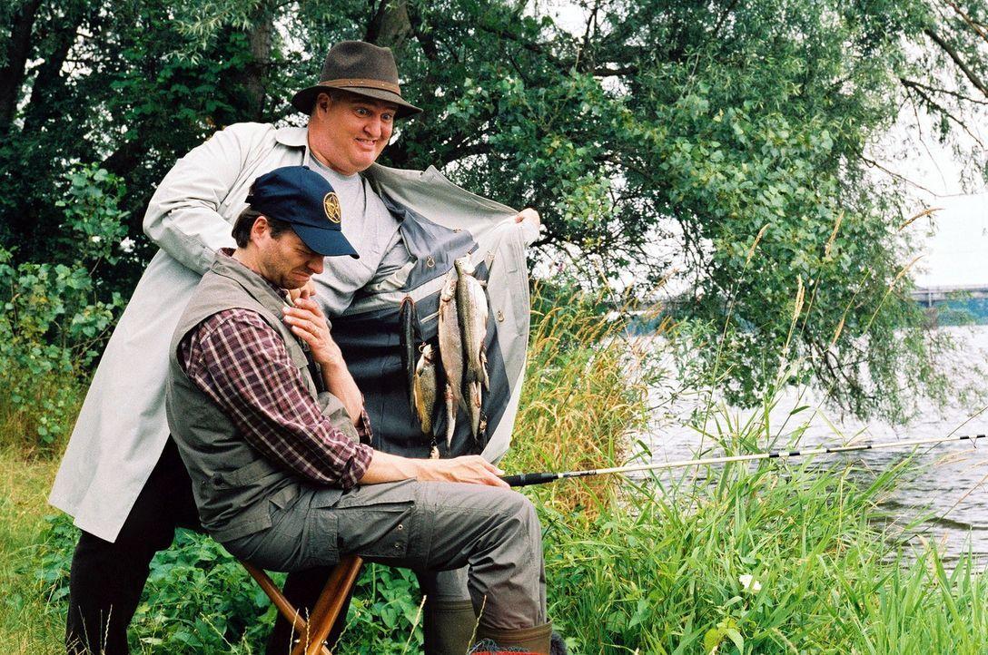 Markus Maria Profitlich (hinten) will Philipp Schepmann (vorne) ein paar Fische verkaufen. - Bildquelle: Gordon Mühle Sat.1
