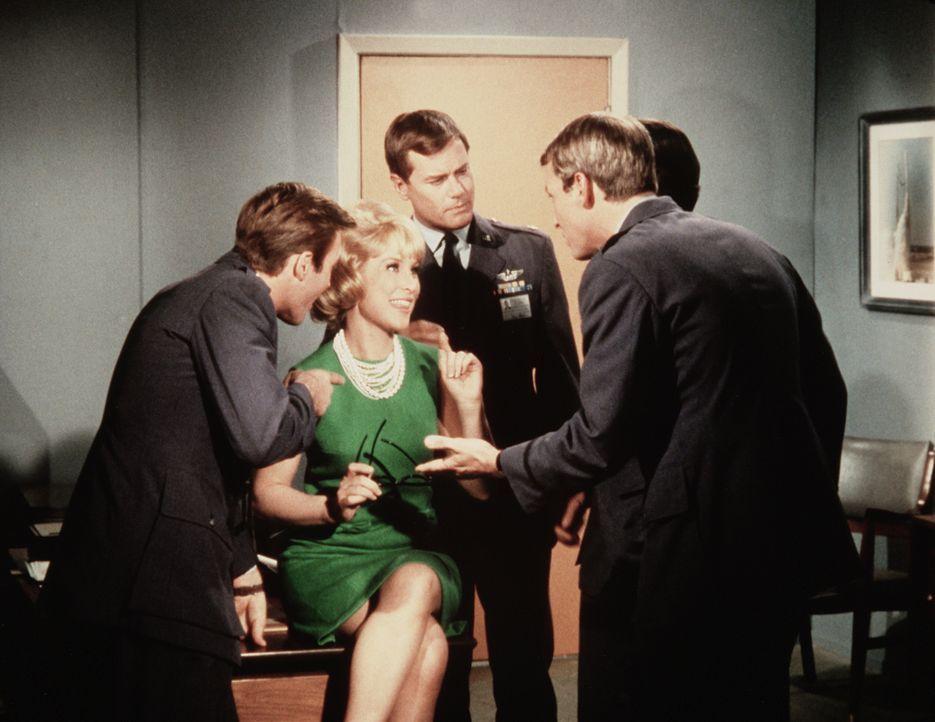 Jeannie (Barbara Eden, l.) ist die neue Sekretärin des Generals, von den jungen NASA-Offiziere umschwärmt. Ihrem Meister Tony (Larry Hagman, M.) ist... - Bildquelle: Columbia Pictures