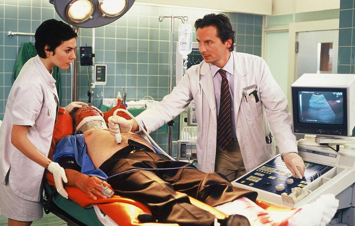 Dr. Meier-Liszt (David C. Bunners, r.) untersucht Norbert Blank (Roland Astor, liegend), der nach einem Unfall in die Klinik eingeliefert wurde. Sch... - Bildquelle: Norbert Kuhroeber Sat.1