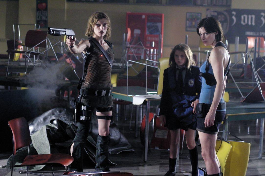 Um lebend aus der Stadt kommen zu können, müssen (v.l.n.r.) Alice (Milla Jovovich), Angie (Sophie Vavasseur) und Jill (Sienna Guillory) es nicht nur... - Bildquelle: Constantin Film