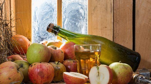 eine Flasche Cider zwischen Äpfeln