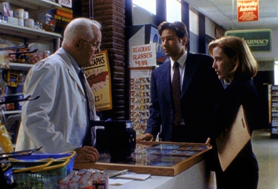 Ein Drogist (Walter MacDonald, l.), der die letzten Fotos von der Entführten machte, bevor sie verschwand, zeigt Mulder (David Duchovny, M.) und Scu... - Bildquelle: TM +   2000 Twentieth Century Fox Film Corporation. All Rights Reserved.