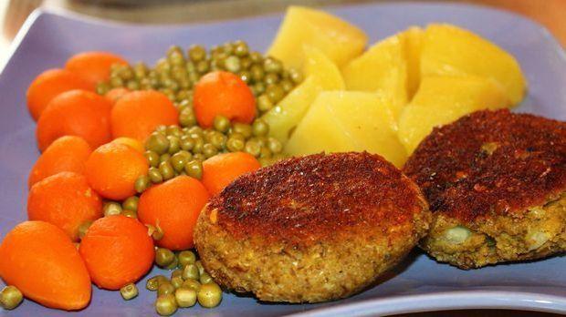 Gemüsefrikadellen auf einem Teller mit Erbsen, Möhren und Kartoffeln als Beil...