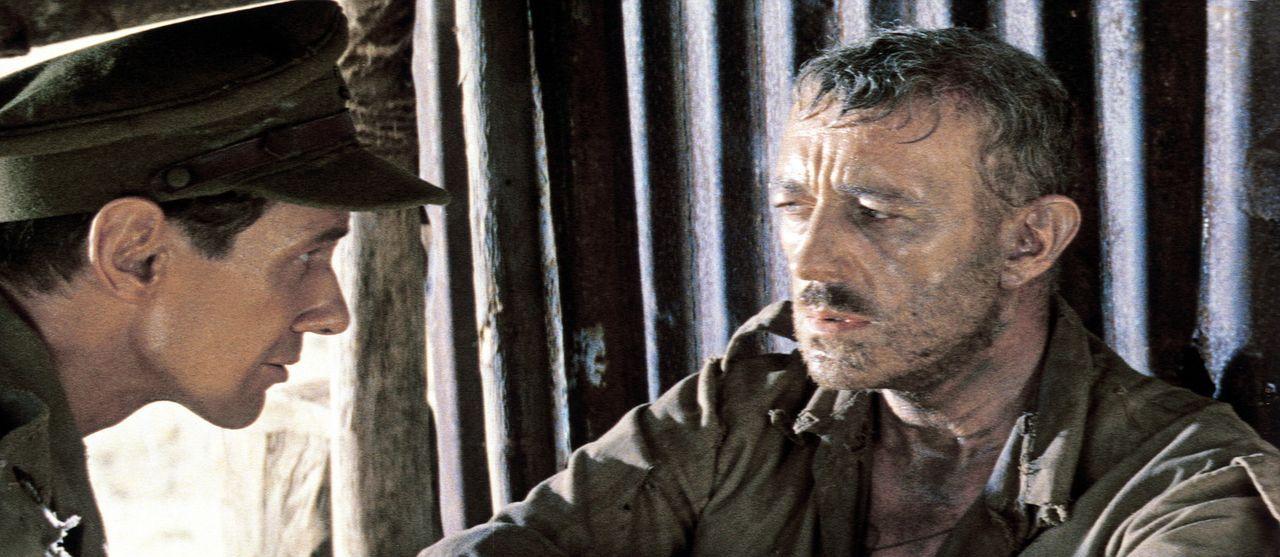 Major Clipton (James Donald, l.) untersucht den schwer angeschlagenen Oberst Nicholson (Alec Guinness, r.) ...