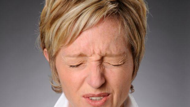 Frau kneift Augen fest zusammen