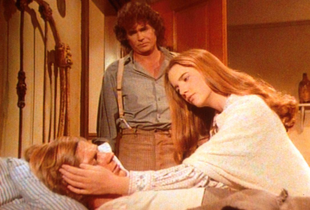 Almanzo (Dean Butler, liegend) ist an einer schweren Lungenentzündung erkrankt. Laura (Melissa Gilbert, r.) und Charles (Michael Landon, M.) sind a... - Bildquelle: Worldvision