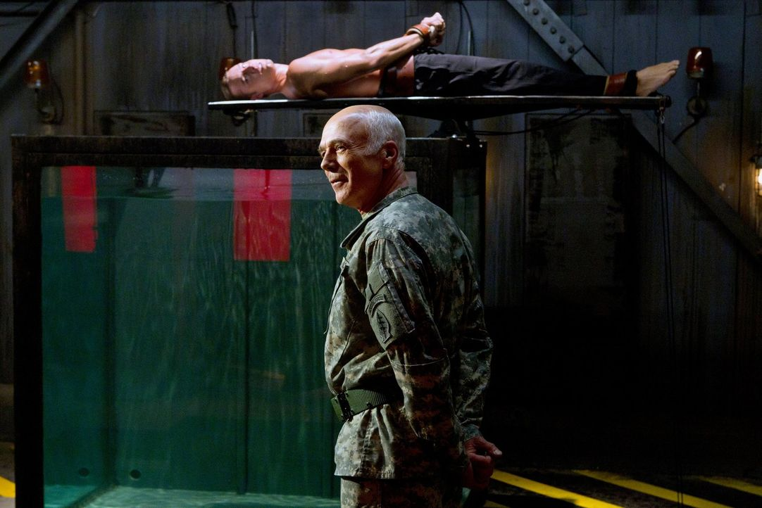 Hinter der Registration der Superhelden versteckt sich nichts anderes, als eine Folter durch Colonel Slade (Michael Hogan, vorne). Oliver (Justin Ha... - Bildquelle: Warner Bros.