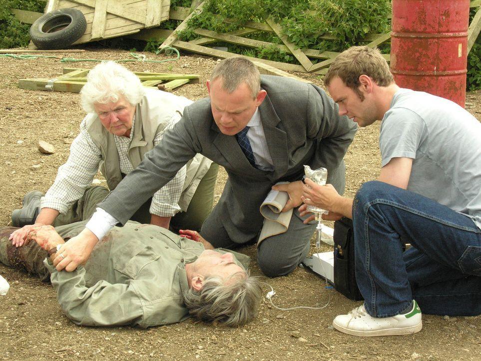 Können (v.l.n.r.) Tante Joan (Stephanie Cole), Doc Martin (Martin Clunes) und Al (Joe Absolom) dem Farmer Phil Pratt (Roger Lloyd Pack, liegend) das... - Bildquelle: BUFFALO PICTURES/ITV