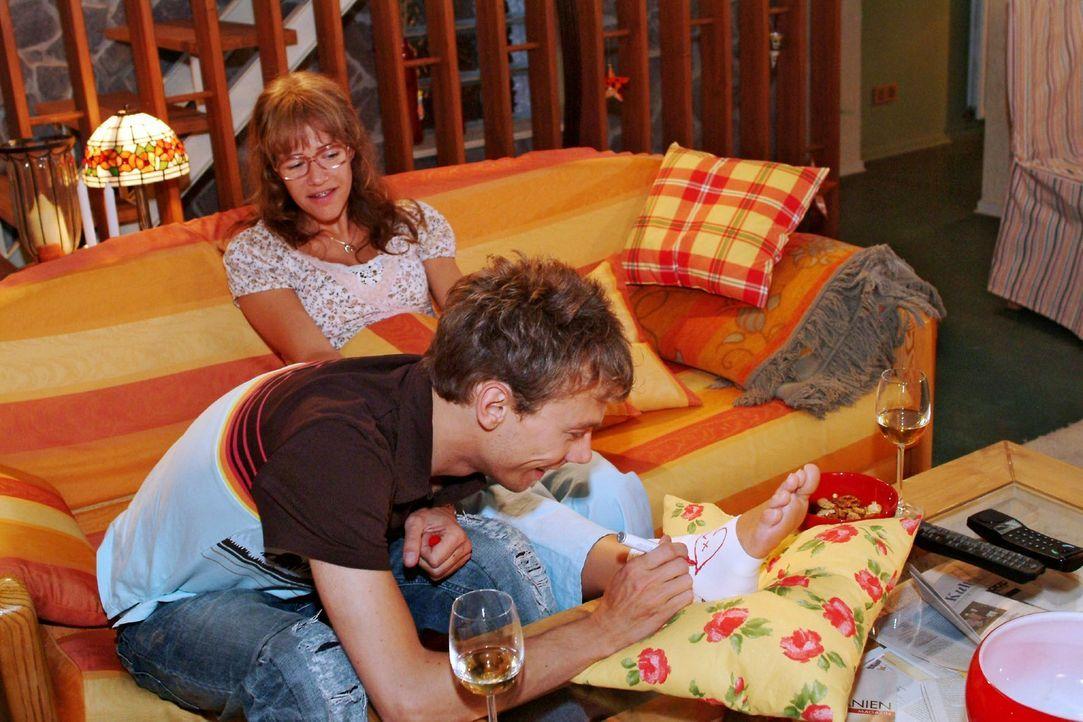 Romantische Momente: Jürgen (Oliver Bokern, vorne) malt Lisa (Alexandra Neldel, hinten) Herzchen auf die Bandage ihres verletzten Fußes. (Dieses F... - Bildquelle: Monika Schürle Sat.1