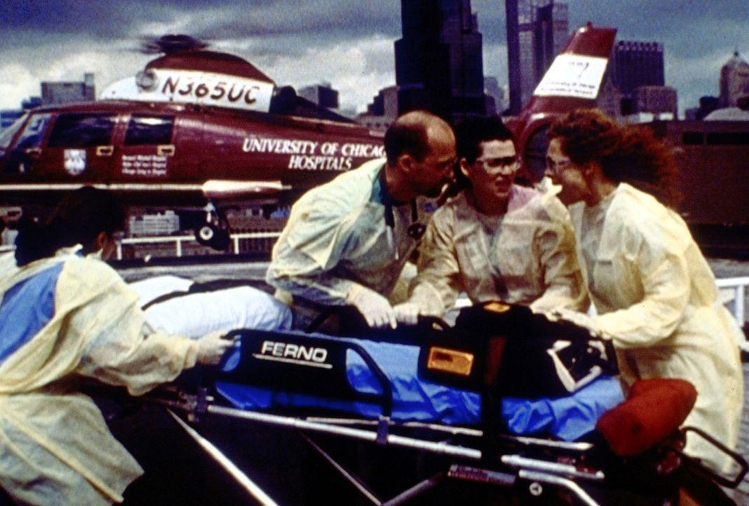 Greene (Anthony Edwards, 2.v.l.), Hathaway (Julianna Margulies, 2.v.r.) und Corday (Alex Kingston, r.) nehmen auf dem Dach des Krankenhauses Paul Ca... - Bildquelle: TM+  2000 WARNER BROS.