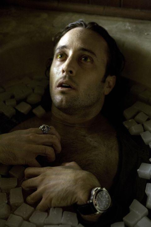 Vom Fieber erschöpft, wagt Mick (Alex O'Loughlin) eine ungewöhnliche Therapie: Er legt sich in eine mit kaltem Wasser und zahlreichen Eiswürfeln gef... - Bildquelle: Warner Brothers