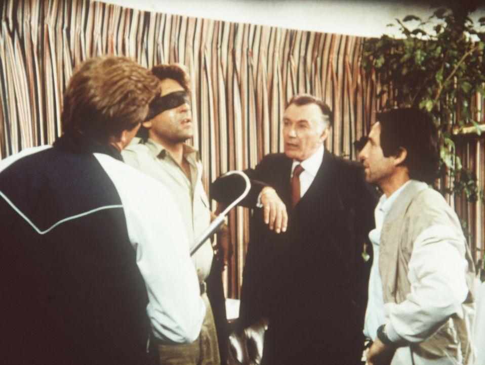 Der Journalist Bart Stoler (Kenneth David Gilman, 2.v.l.) wird vom Botschafter Harcourt (Rick Jason, 2.v.r.) und seinen Handlangern gefoltert, damit...