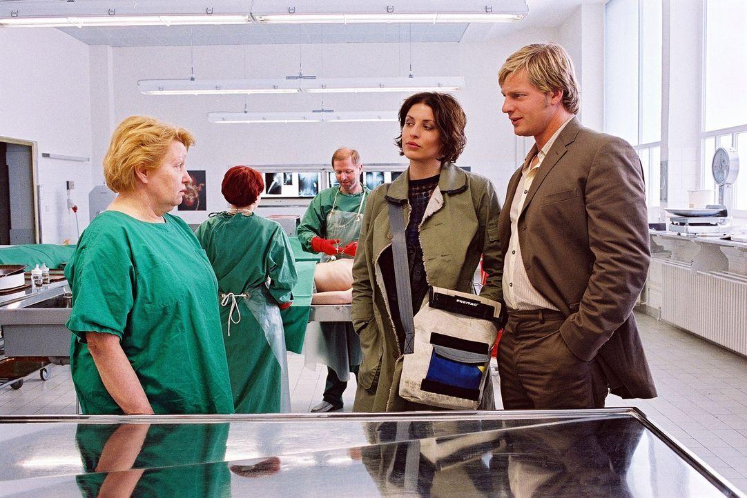 Dr. Reiter (Sarah Camp, l.) hat die Leiche obduziert und gibt den beiden Kommissaren (Elena Uhlig, M.; Henning Baum, r.) Auskunft. - Bildquelle: Christian A. Rieger Sat.1