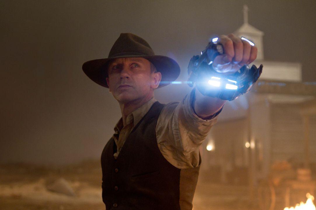 Als die Aliens das kleine Städtchen Absolution angreifen, wird plötzlich Lonergans (Daniel Craig) Armmanschette aktiv. Sie beginnt zu leuchten und o... - Bildquelle: (2011) DREAMWORKS II DISTRIBUTION CO., LLC and UNIVERSAL STUDIOS.