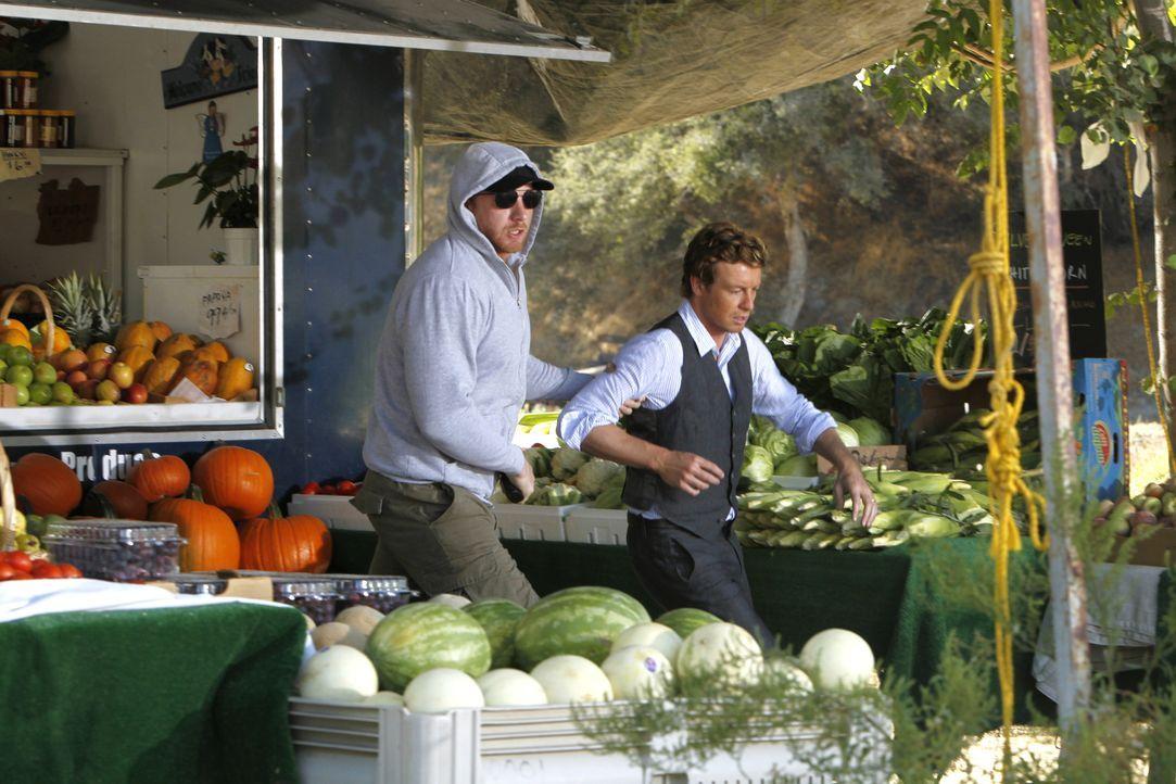 Patrick Jane (Simon Baker, r.) wird an einem Obststand vom Gangster Fred Kittel (Adam Dunnells, l.) entführt, nachdem dieser den Obsthändler erschos... - Bildquelle: Warner Bros. Television