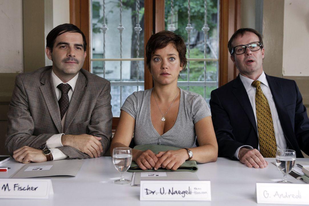 Paula (Muriel Baumeister, M.) nimmt auf der Pressekonferenz der Gemeindeversammlung zwischen Dr. Fischer (Beat Marti, l.) und dem Bürgermeister (Peter Jecklin, r.) zum Bärenproblem Stellung ...