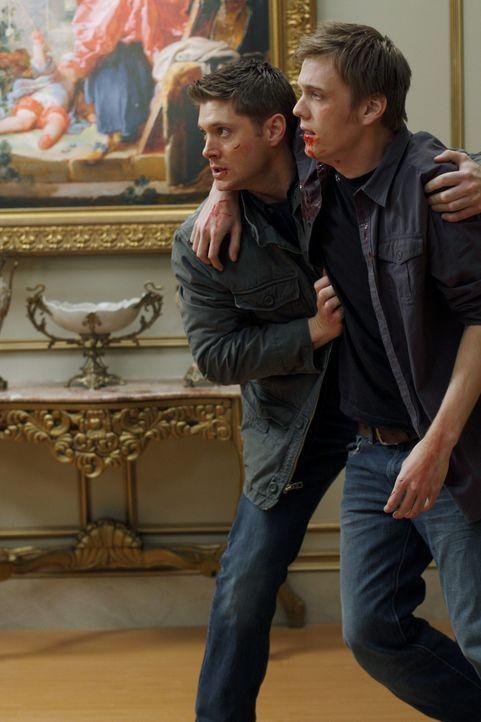 Dean (Jensen Ackles, l.) hat eingewilligt, seine Hülle Michael zu übergeben. Zur Sicherheit hat Zachariah Adam (Jake Abel, r.), den Bruder von Dean... - Bildquelle: Warner Brothers