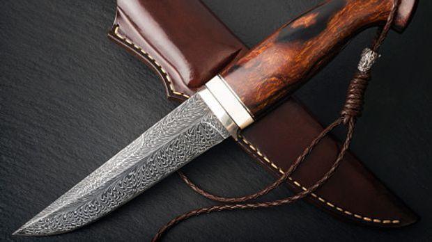 Damastmesser mit braunem Holgriff liegt quer über braunem Messeretui