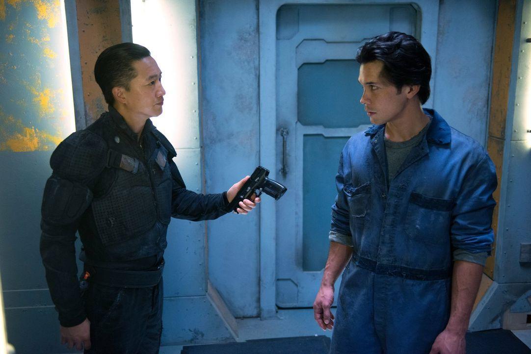 Commander Shumway (Terry Chen, l.) weiß ganz genau, dass Bellamy (Bob Morley, r.) alles für seine Schwester tun würde, und das macht er sich zunutze... - Bildquelle: Warner Brothers