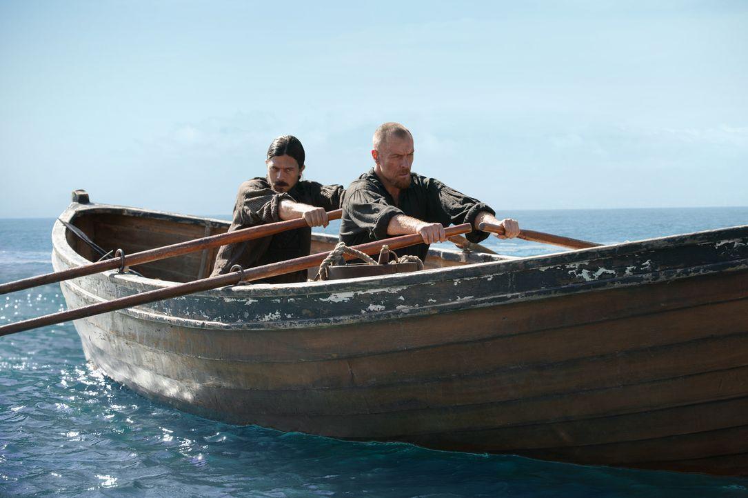 John Silver (Luke Arnold, l.) wird von Captain Flint (Toby Stephens, r.) bis an die Grenzen seiner Belastbarkeit getrieben, während sich Nassau auf... - Bildquelle: David Bloomer 2016 Starz Entertainment, LLC. All Rights Reserved