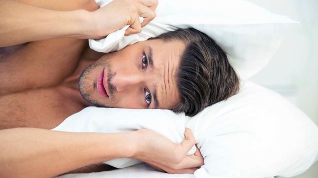 Junger Mann liegt im Bett und ist verstört
