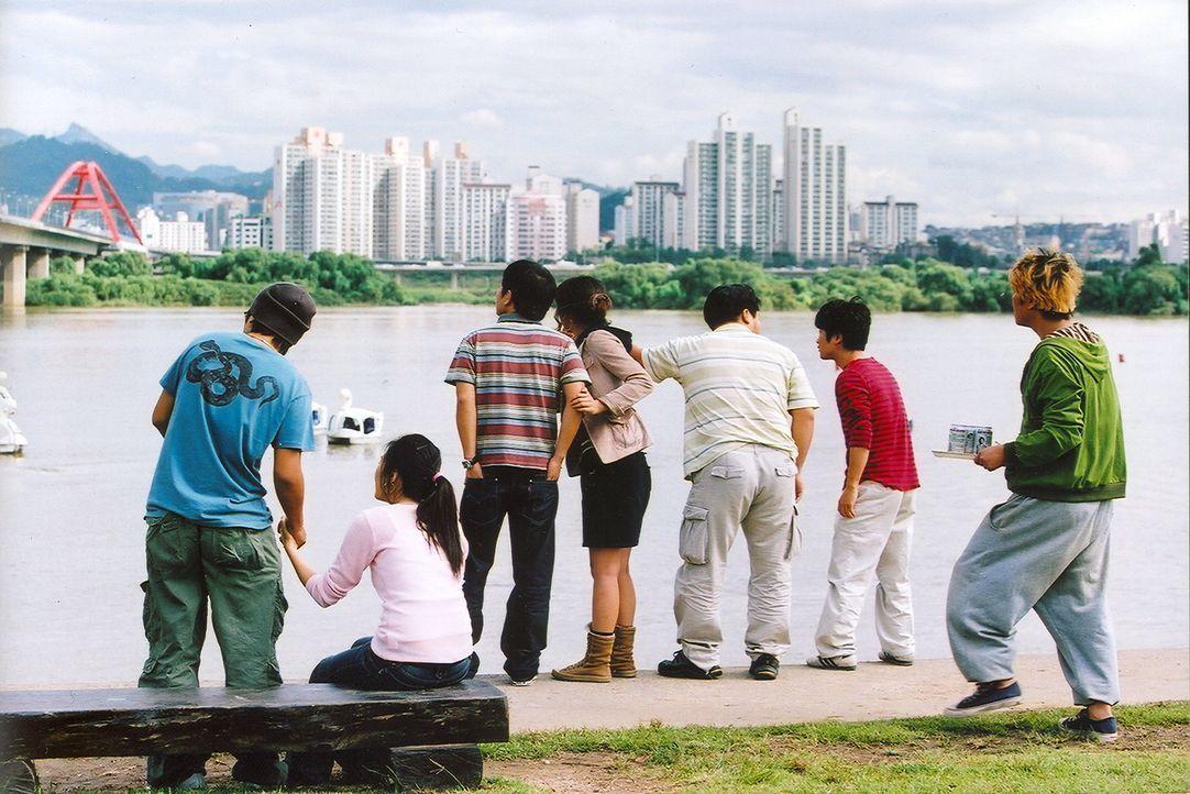 Am Ufer des Han-Flusses drängelt sich eine Schar von Schaulustigen, um nach dem Monster Ausschau zu halten, das gerade ins Wasser gesprungen ist ... - Bildquelle: MFA