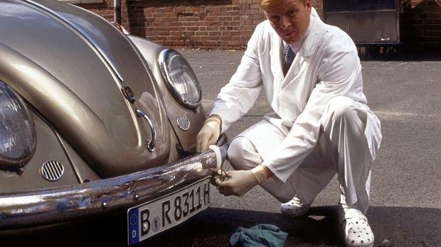 Dieter (Michael Schiller), der Stationsbote, tüftelt an einem VW-Käfer.  Waru...