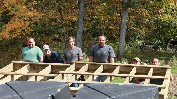Gemeinsam packen die Bauarbeiter um Nate (3.v.r.) tatkräftig an, um das Haus...