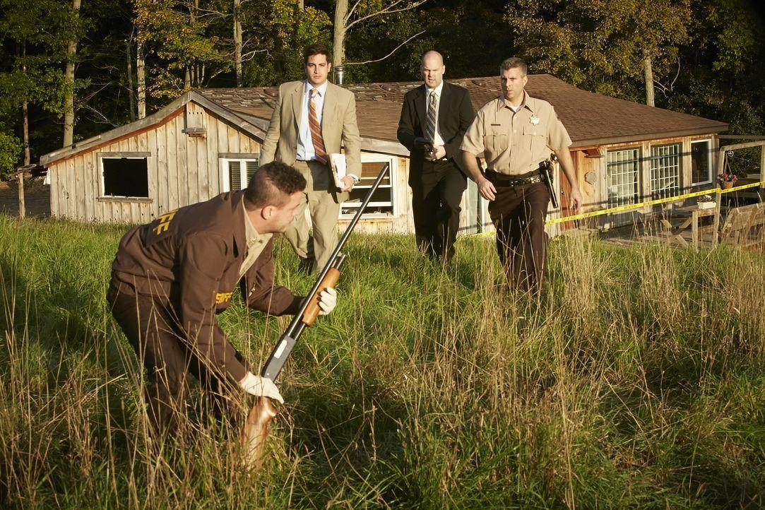 Sichern auf dem Grundstücks der ermordeten Lisa Techel (23) die Tatwaffe: Sheriff Don Philips (Michael Sercerchi) und die Ermittler Chris Thomas (St... - Bildquelle: Ian Watson Cineflix 2015