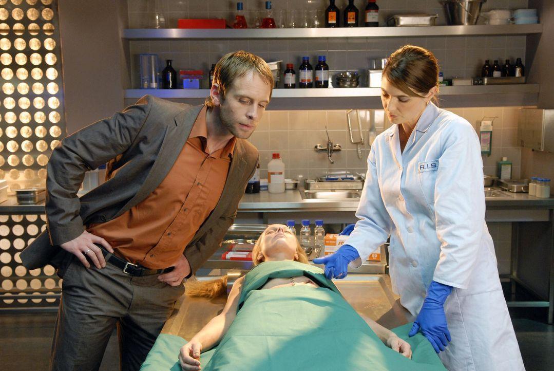 Dr. Stefanie Peters (Nicole Marischka, r.) berichtet Philip Jacobi (Julian Weigend, l.), dass die Tote (Franziska Jünger, M.) an einer Perforation d... - Bildquelle: Christoph Assmann Sat.1