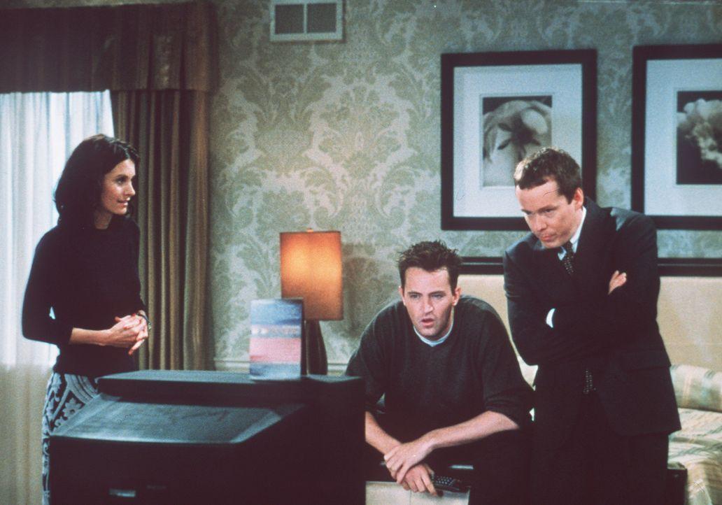 Monica (Courteney Cox, l.) ist ziemlich wütend auf Chandler (Matthew Perry, M.), denn er starrt mit seinem Freund die ganze Zeit in den Fernseher. - Bildquelle: TM+  2000 WARNER BROS.