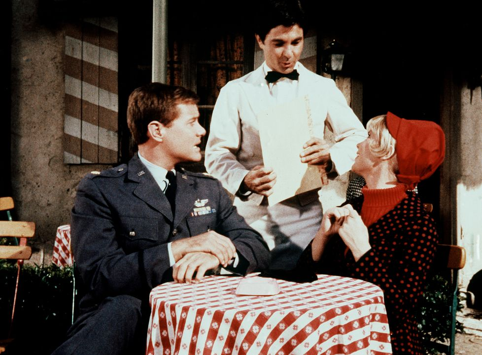 Jeannie (Barbara Eden, r.) hat Tony (Larry Hagman, l.) in zwei Hälften gespalten, damit sie mit ihm in Paris fein essen kann, während er gleichzeitig an einer Konferenz teilnimmt.