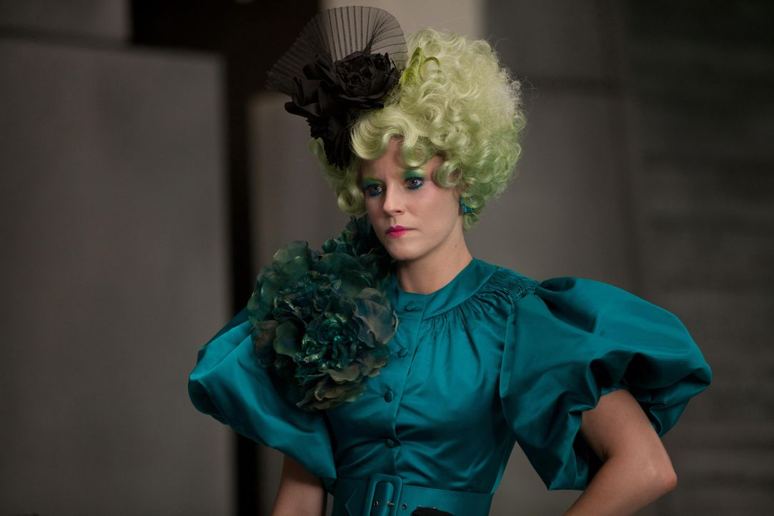 Katniss' und Peetas Betreuerin ist Effie Trinket (Elizabth Banks). Sie trägt immer eine Perücke in einer knalligen Farbe und dazu passendes Makeup... - Bildquelle: Studiocanal GmbH