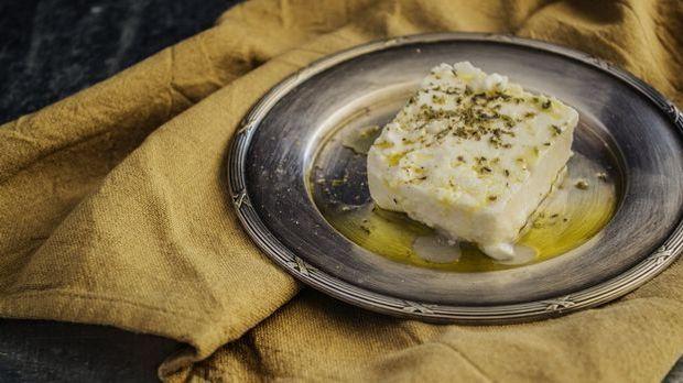 Feta-Käse mit Kräutern und Olivenöl auf einem Teller angerichtet