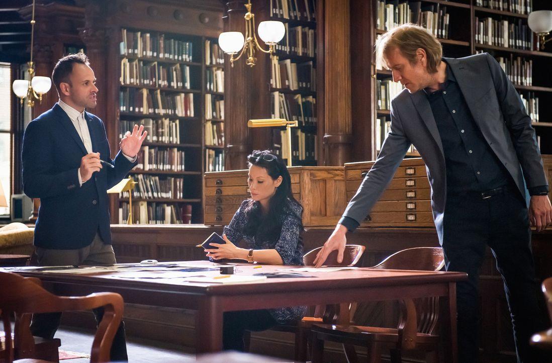 Brainstorming in der Bibliothek: Holmes (Jonny Lee Miller, l.), Watson (Lucy Liu, M.) und Mycroft (Rhys Ifans, r.) versuchen fieberhaft herauszufind... - Bildquelle: CBS Television