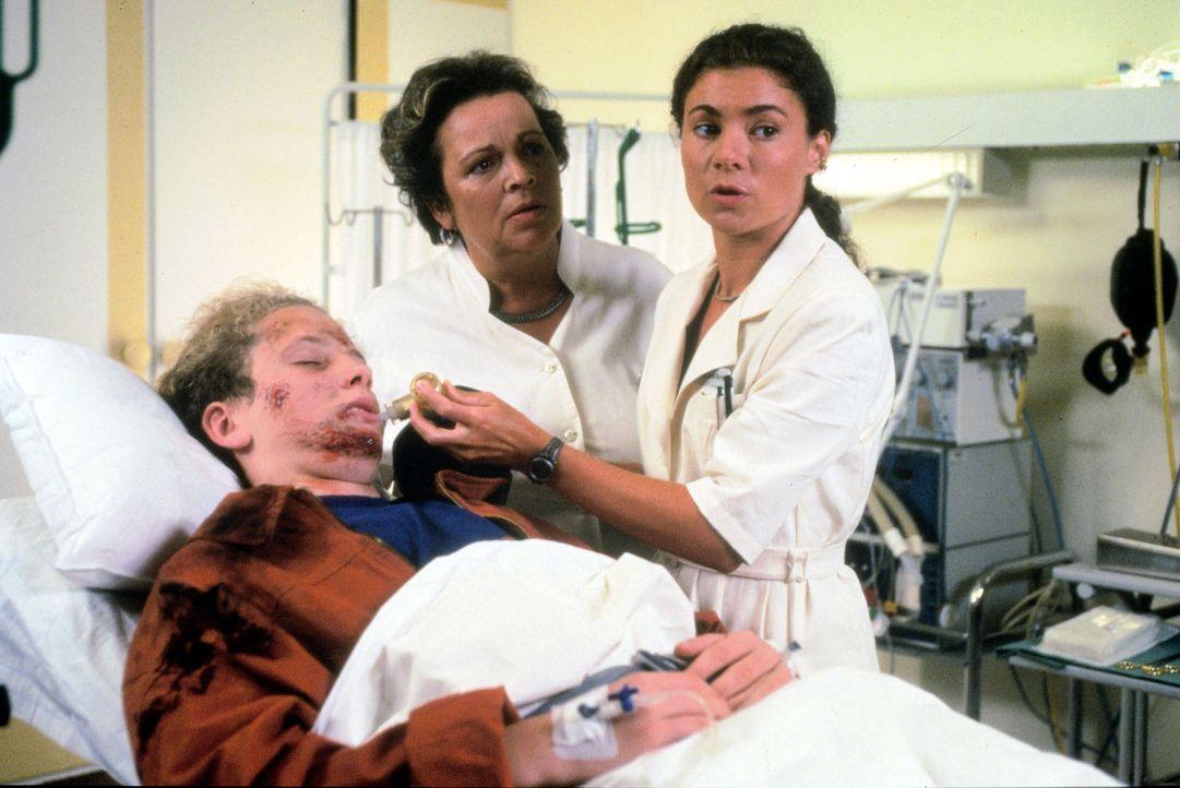 Sebastian (Gabriel Schauf, l.), der 16-jährige Sohn von Oberarzt Dr. Stein, wird von einem Motorradfahrer schwer verletzt. Schwester Stefanie (Kathrin Waligura, r.) und Schwester Klara (Walfriede Schmitt, M.) sind bei ihm und warten auf die Entscheidung, welcher Arzt die komplizierte Operation durchführen wird.