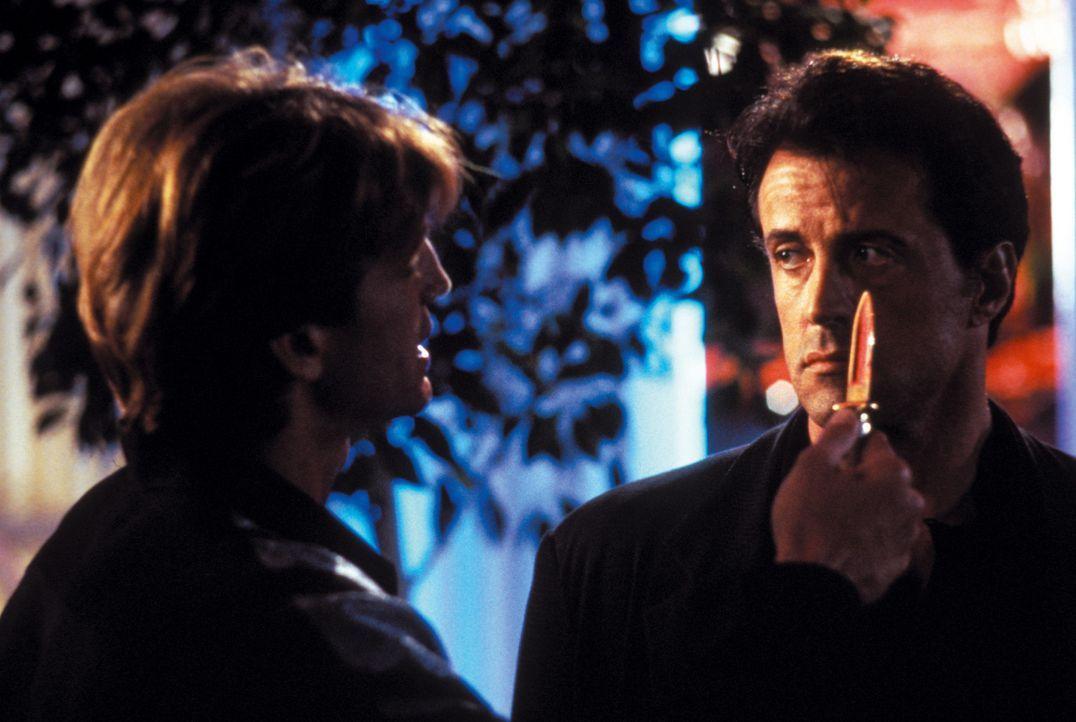 Die äußerst attraktive May Munro bittet den Profi-Killer Ray Quick (Sylvester Stallone, r.), den Mörder ihrer Eltern, Thomas Leon (Eric Roberts,... - Bildquelle: Warner Brothers