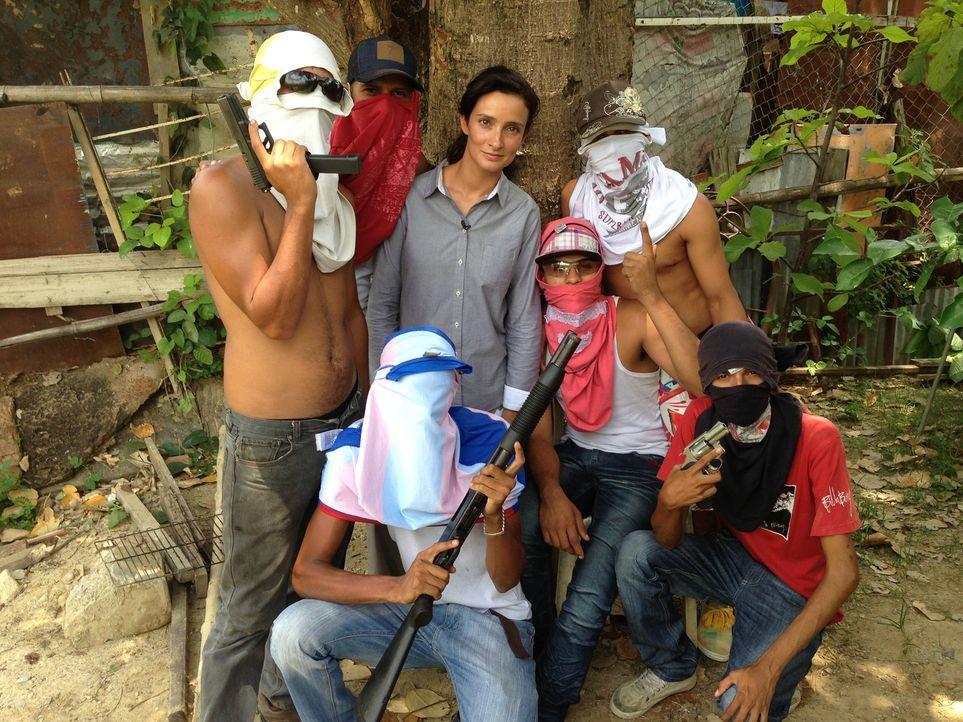 Die Reporterin Kiki King (stehend 2.v.r.) wagt sich in Venezuelas Untergrund und interviewt Gangmitglieder ... - Bildquelle: Quicksilver Media 2012