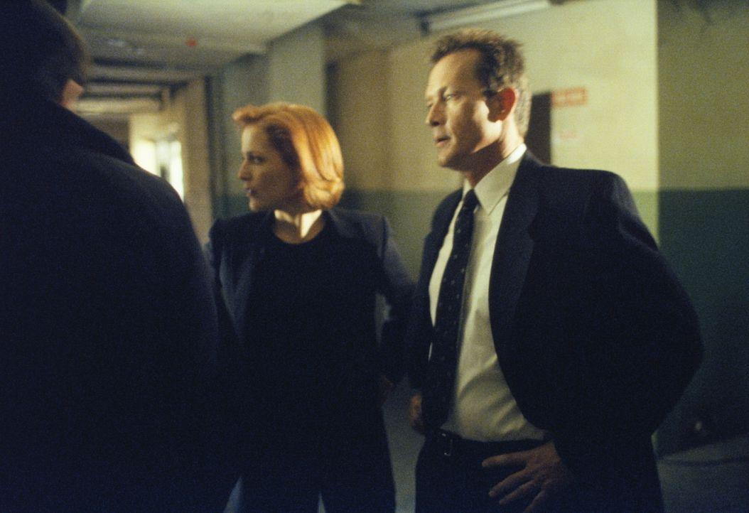 Scully (Gillian Anderson, M.) und Doggett (Robert Patrick, r.) erfahren von dem Häftling Martin Wells, dass er sich in der Zeit rückwärts bewegt. - Bildquelle: TM +   2000 Twentieth Century Fox Film Corporation. All Rights Reserved.