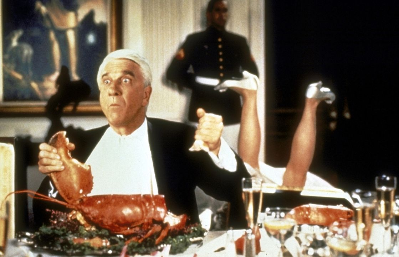Als Belohnung für die Erschießung des 1000. Drogendealers erhält Lt. Frank Drebin (Leslie Nielsen, l.) eine Einladung zum Abendessen beim Präsid... - Bildquelle: United International Pictures
