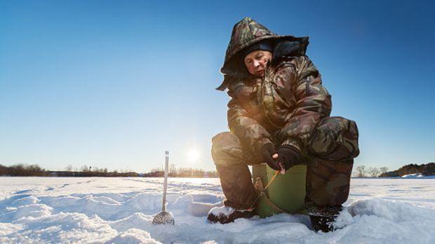 Mann in dicker Winterkleidung sitzt auf Schnee und Eis und angelt