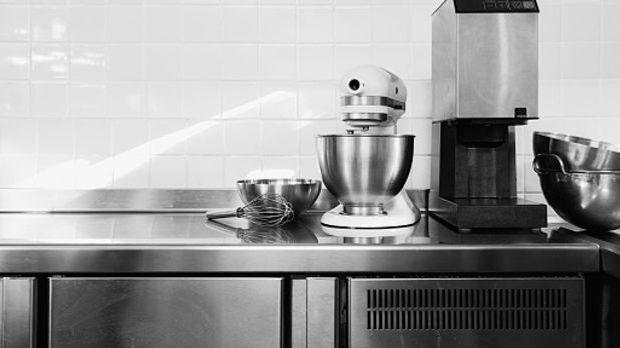 unterschiedliche Küchenutensilien in Silber aufgereiht auf einer Arbeitsplatte