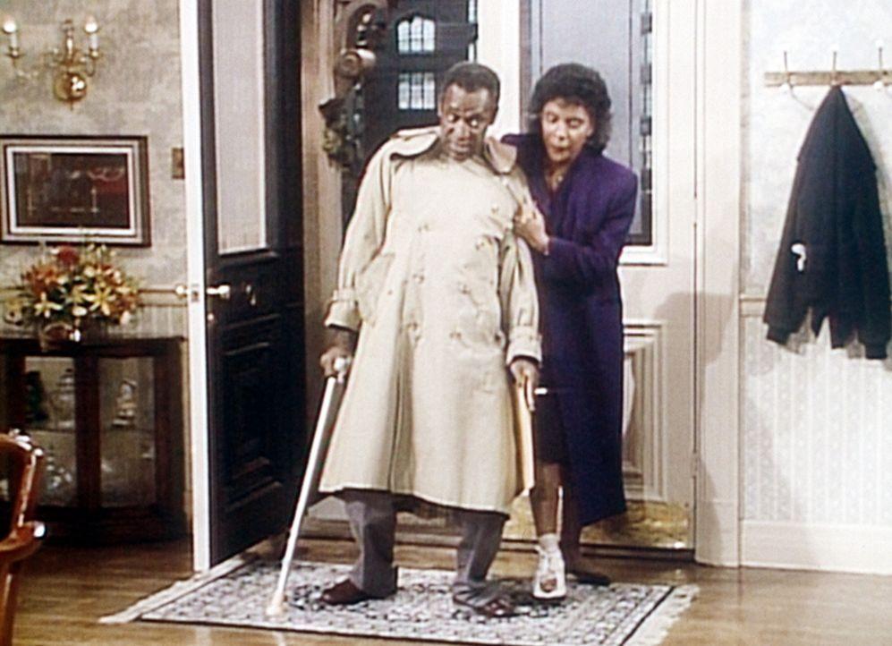 Clair (Phylicia Rashad, r.) hat sich den Zeh gebrochen, so dass Cliff (Bill Cosby, l.) ihre Krücken tragen muss, während er ihr als Stütze dient. - Bildquelle: Viacom