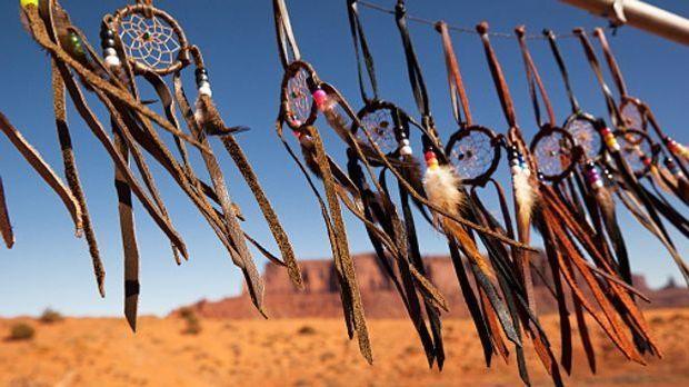 An einer Schnur befestigte Traumfänger mit Federn wehen vor einer Wüste im Wind