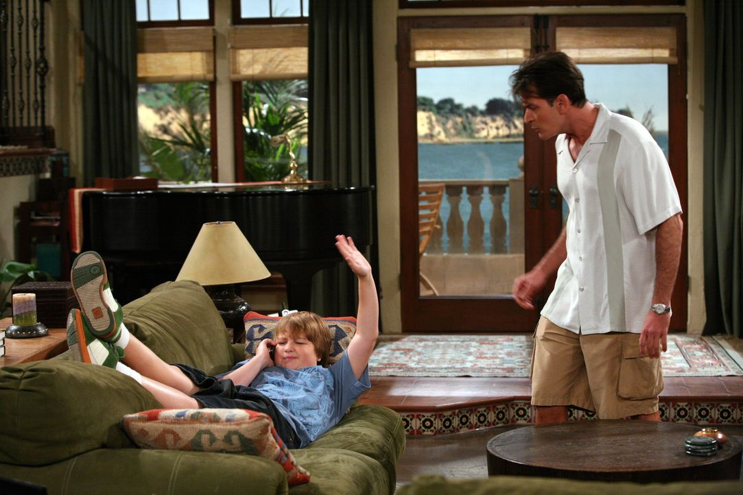 Jake (Angus T. Jones, l.) hat eine Freundin und tauscht mit ihr am Telefon sexuelle Anspielungen aus. Charlie (Charlie Sheen, r.) kann es nicht fass... - Bildquelle: Warner Brothers Entertainment Inc.