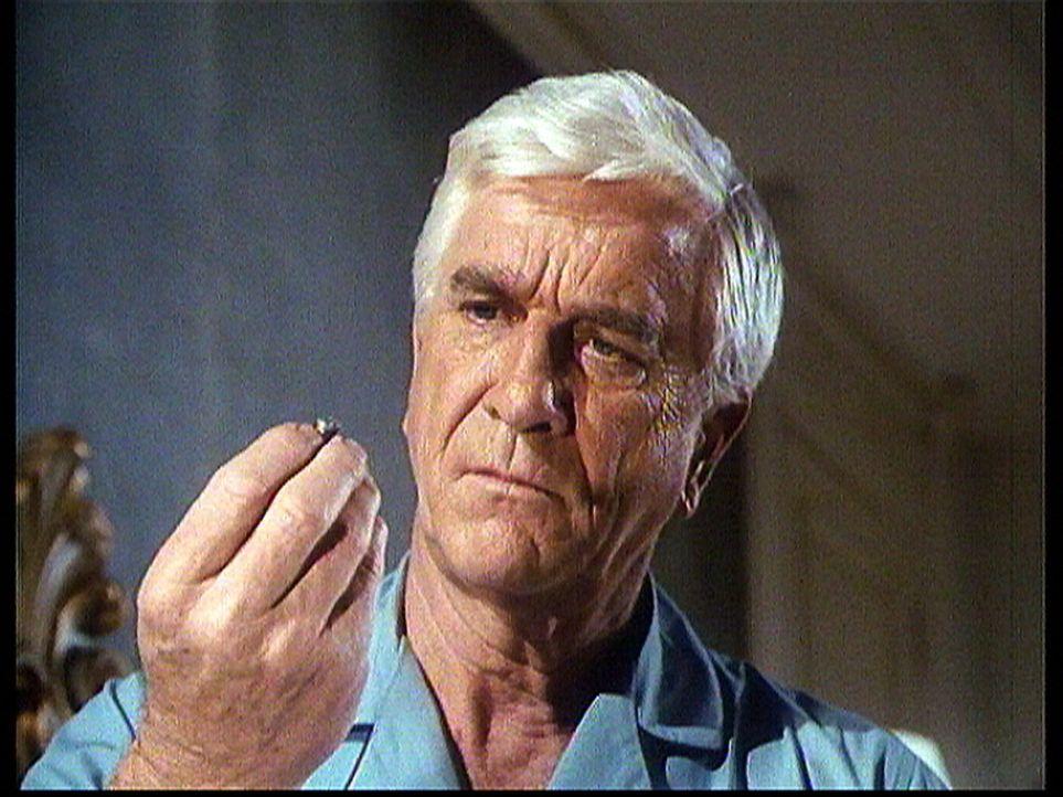 R. R. Benson (Leslie Nielsen) betrachtet die Kugel, an der er hätte sterben können, die aber von seiner Bibel abgefangen wurde. - Bildquelle: Worldvision Enterprises, Inc.