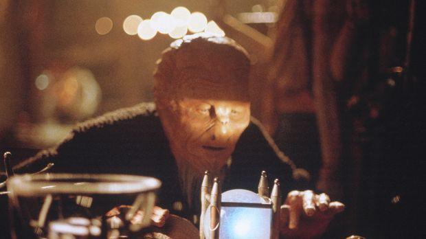 Ein Alien (Alex Diakun) in Gestalt eines Ladenbesitzers prüft auf recht eigen...